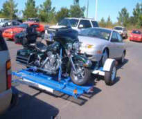 Tandem Tow Dolly carries vehicle and bike.